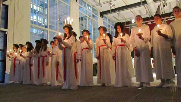 En esta imagen se aprecia las chicas con sus vestidos blancos y el fajín rojo y Santa Lucia destaca con su corona de velas. En tanto, los chicos se ven con sus vestidos con capirotes.